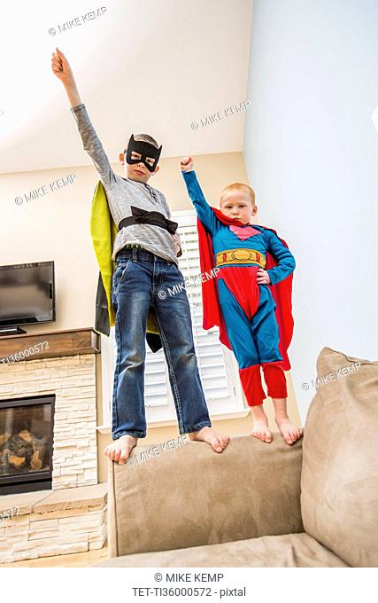 Boys (2-3, 6-7) wearing superhero costumes standing on sofa