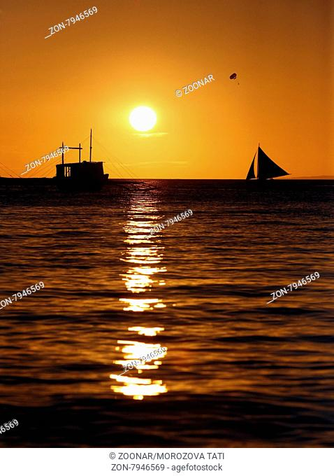 Drifting boat on a sunset. Coast of the Pacific ocean. Island Boracay
