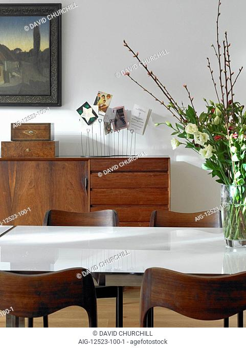 Polished wooden chest of drawers and chairs with cut flowers on table in Garden House, UK