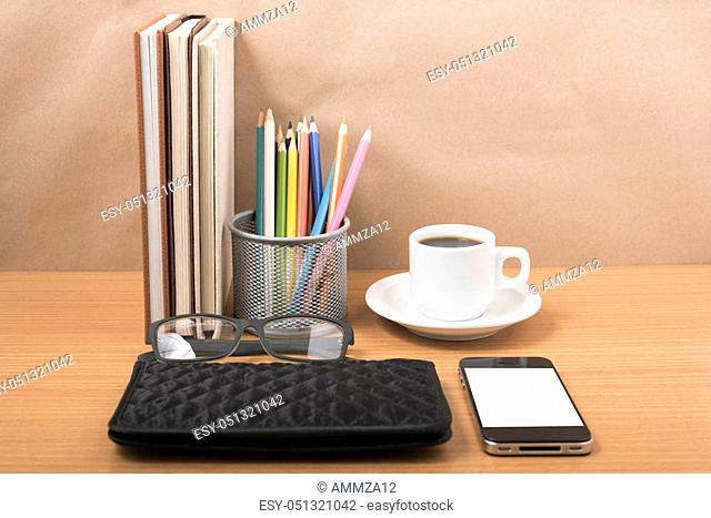 office desk: coffee with phone, stack of book, eyeglasses, wallet, color pencil box on wood background