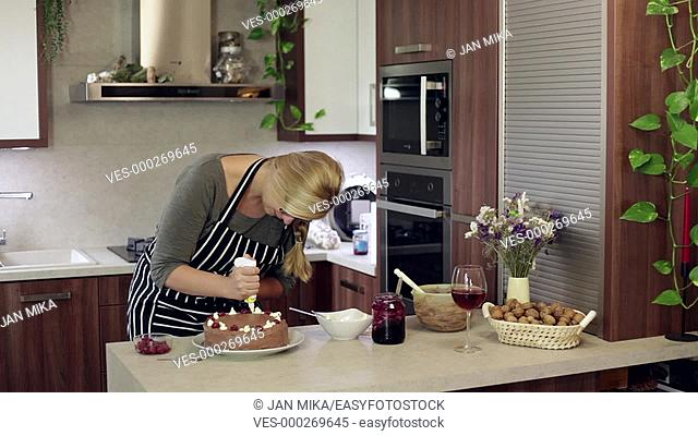 Young happy woman decorating homemade cake in the kitchen at home