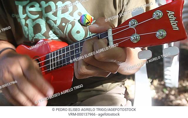 Un chico toca una guitarra pequeña