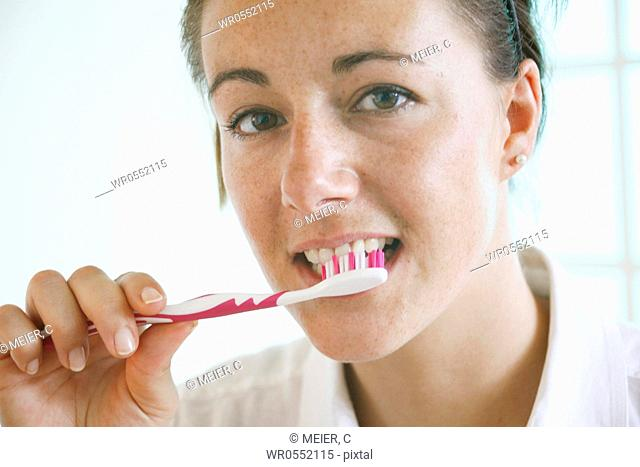 Young woman brushes her teeth