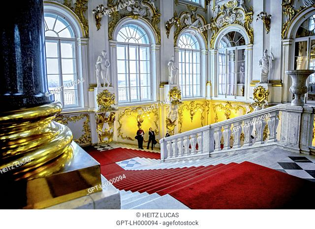 VISITORS LOOKING AT THE RICHLY DECORATED STAIRWAY OF THE HERMITAGE MUSEUM, SAINT PETERSBURG, RUSSIA