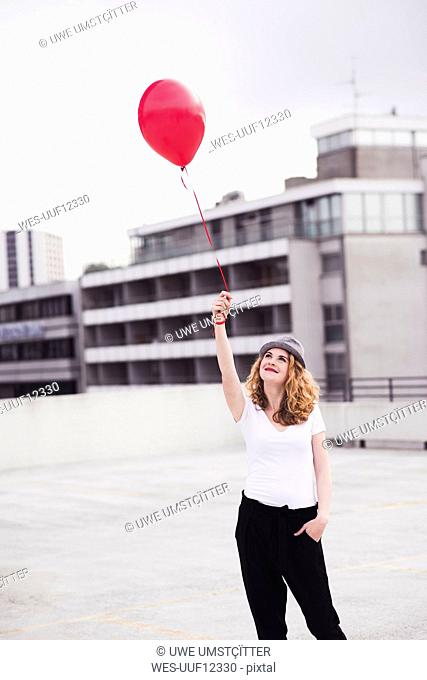 Smiling young woman with red balloon