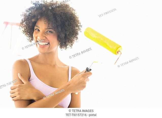 Portrait of woman holding paint roller