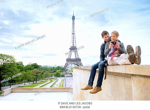 Caucasian couple looking at photographs near Eiffel Tower, Paris, France