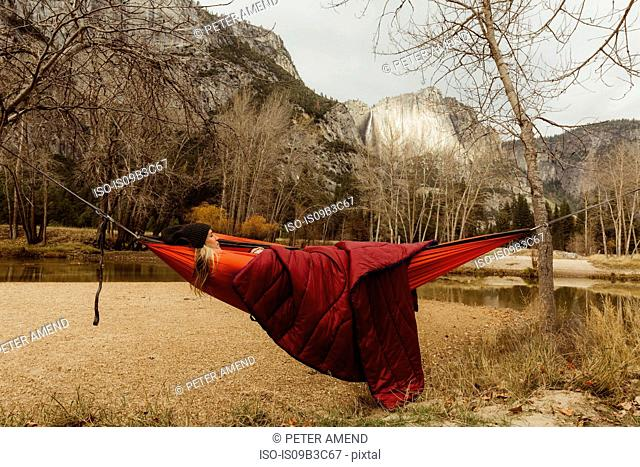 Woman reclining in red hammock looking out at landscape, Yosemite National Park, California, USA