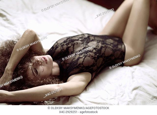 Sensual boudoir portrait of a sexy young beautiful woman lying on a bed in lacy underwear