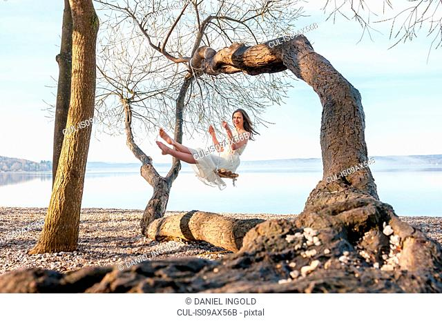 Woman on tree swing by ocean looking at camera smiling