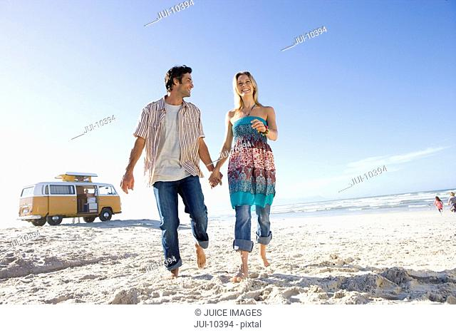 Young couple on beach holding hands, camper van in background, low angle view