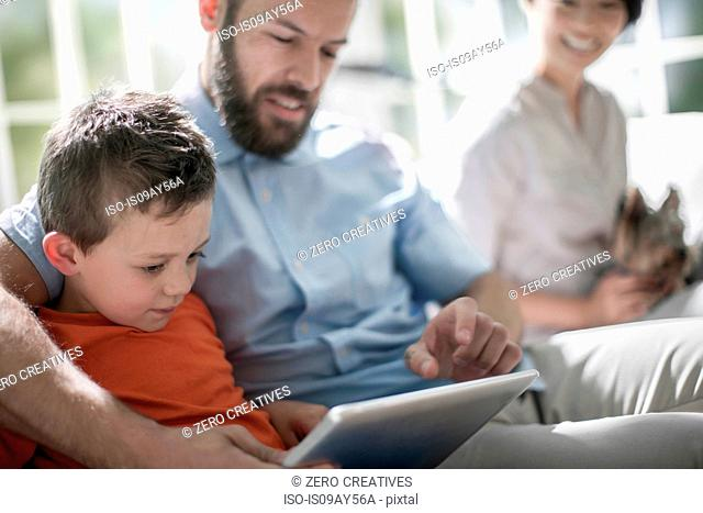 Father and son using digital tablet, mother with pet dog in background
