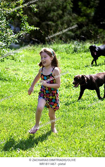 Young girl running with dogs