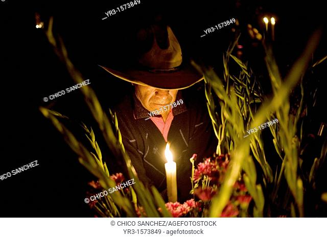 A man decorates the grave of a family member at the cemetery in San Gregorio Atlapulco on the outskirts of Mexico City. on the Day of the Dead celebration