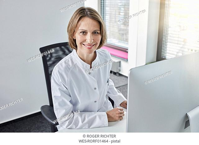 Female doctor working on computer, smiling