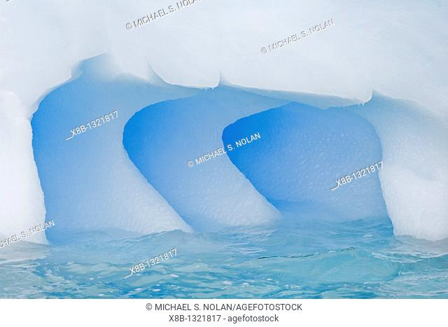 Fanciful designs formed by wind and sea in this iceberg south of the Antarctic Circle on the west side of the Antarctic Peninsula during the summer months  More...