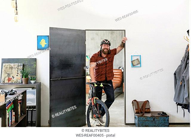 Portrait of laughing man with bicycle in office