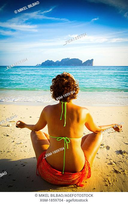 Young woman doing yoga on the beach  Long beach  Phi Phi Don island  Krabi province, Andaman Sea, Thailand