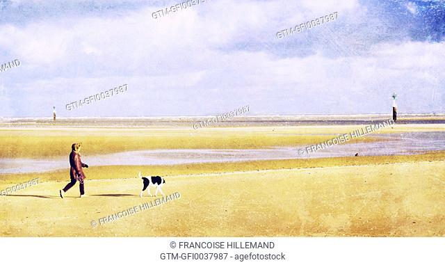 a woman walking her dog on the beach