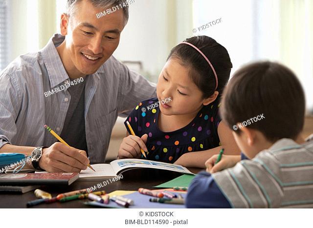 Father helping children do homework