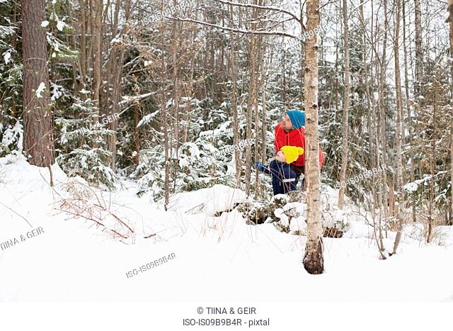 Man and son looking up from snow covered forest