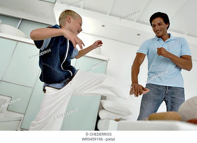 Close-up of a boy practicing karate with his father
