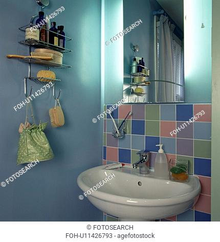 Mirror and pastel tiles above basin in pale turquoise economy-style bathroom