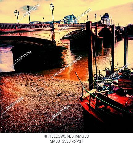 Houseboats at low tide by Battersea Bridge, London, England