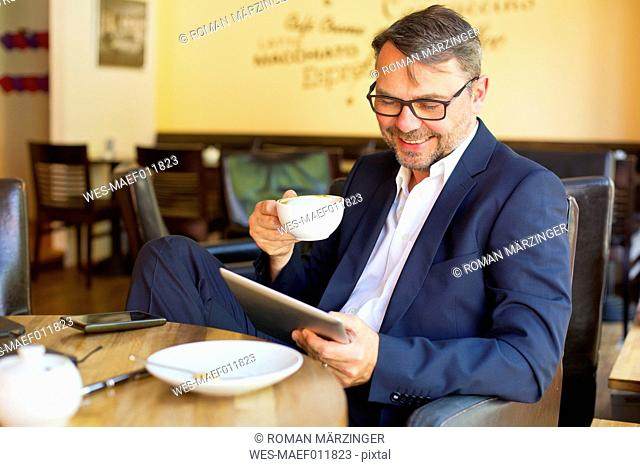 Portrait of smiling businessman using digital tablet while sitting in a cafe drinking coffee