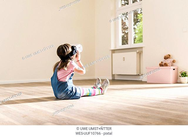 Girl in empty apartment wearing VR glasses