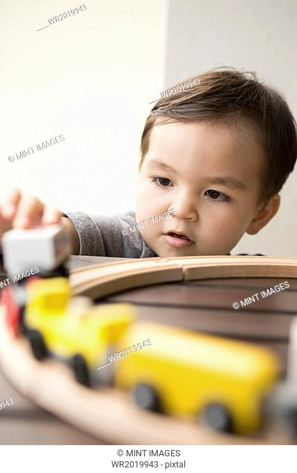 Young boy playing with a wooden train set