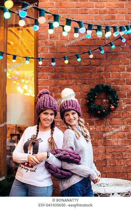 Two women in purple knitted hats, purple infinity scarf and blue jeans make posing with brick wall and Christmas garland on the background