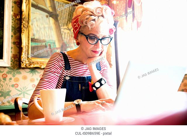 Quirky woman using laptop in bar and restaurant, Bournemouth, England