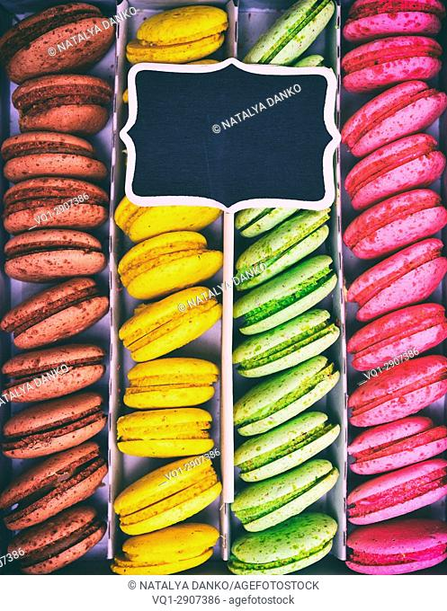 Multi-colored cakes macarons in a paper box, on top of a wooden black plate on a stick, vintage toning