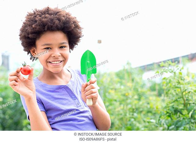 Girl holding tomato and trowel