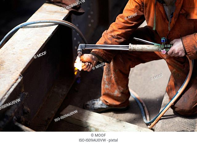Welder lighting welding flame in shipyard workshop