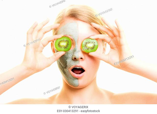 Skin care. Surprised woman in clay mud mask on face covering eyes with slices of kiwi isolated. Girl taking care of dry complexion