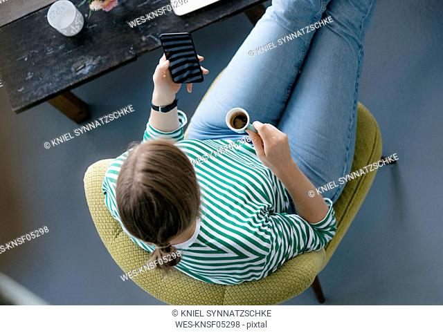 Overhead view of young woman with cell phone and espresso in a cafe