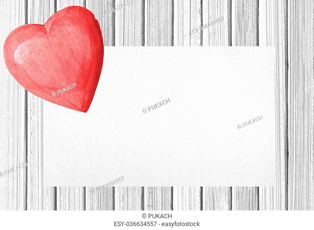 Wooden pink heart and card on white wooden texture close-up