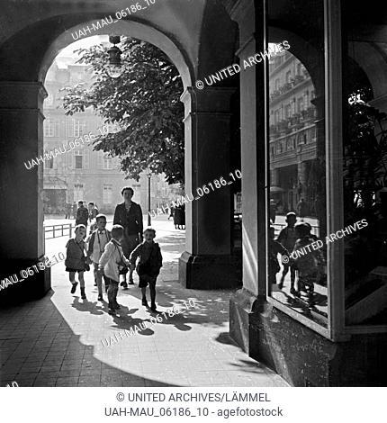 Eine Kindergärtnerin ist mit ihrer Kindergruppe unterwegs in der Innenstadt von Bad Ems, Deutschland 1930er Jahre. A kinergarten teacher strolling with her...