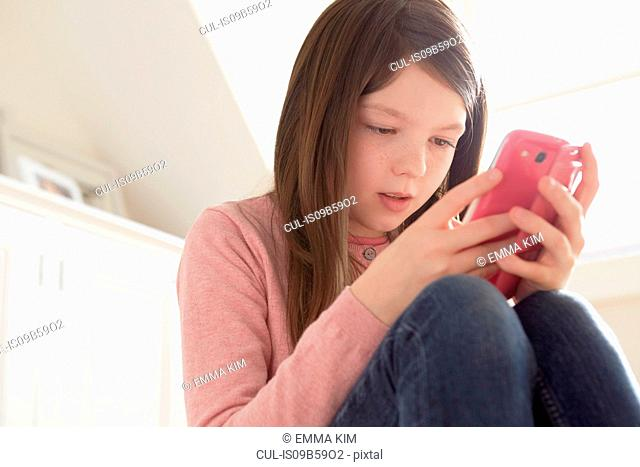 Girl sitting looking at smartphone