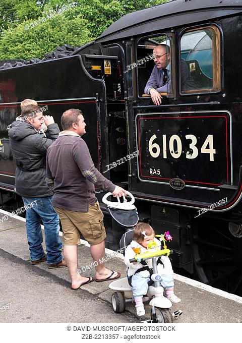 Tourists talk to the driver of a vintage steam engine locomotive, North Yorkshire Moors Railway, on the North Yorkshire Moors, Yorkshire, UK