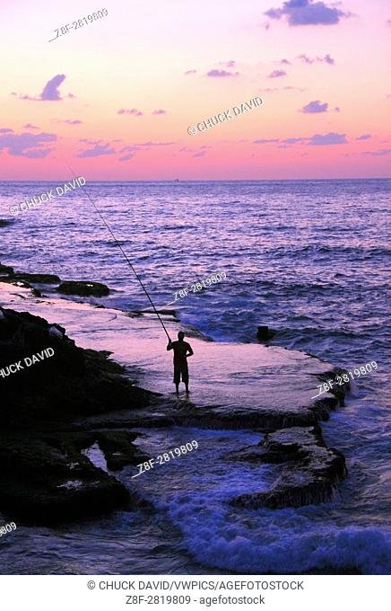 A lone fisherman casts his rod along Beirut's rocky Mediterranean shoreline at sunset, Lebanon
