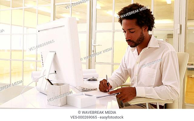 Businessman taking notes at his desk