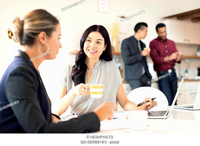 Two young businesswomen having meeting at desk