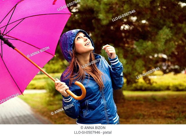 Beautiful woman with umbrella looking at the sky, Debica, Poland