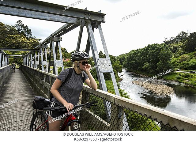 Woman cycles on the Hauraki Rail Trail, bicycling path on the north island in New Zealand