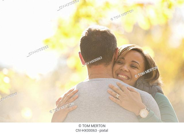 Enthusiastic couple hugging outdoors