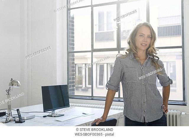 Businesswoman standing in her office, looking at camera