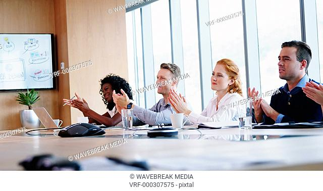 Executives applauding in conference room
